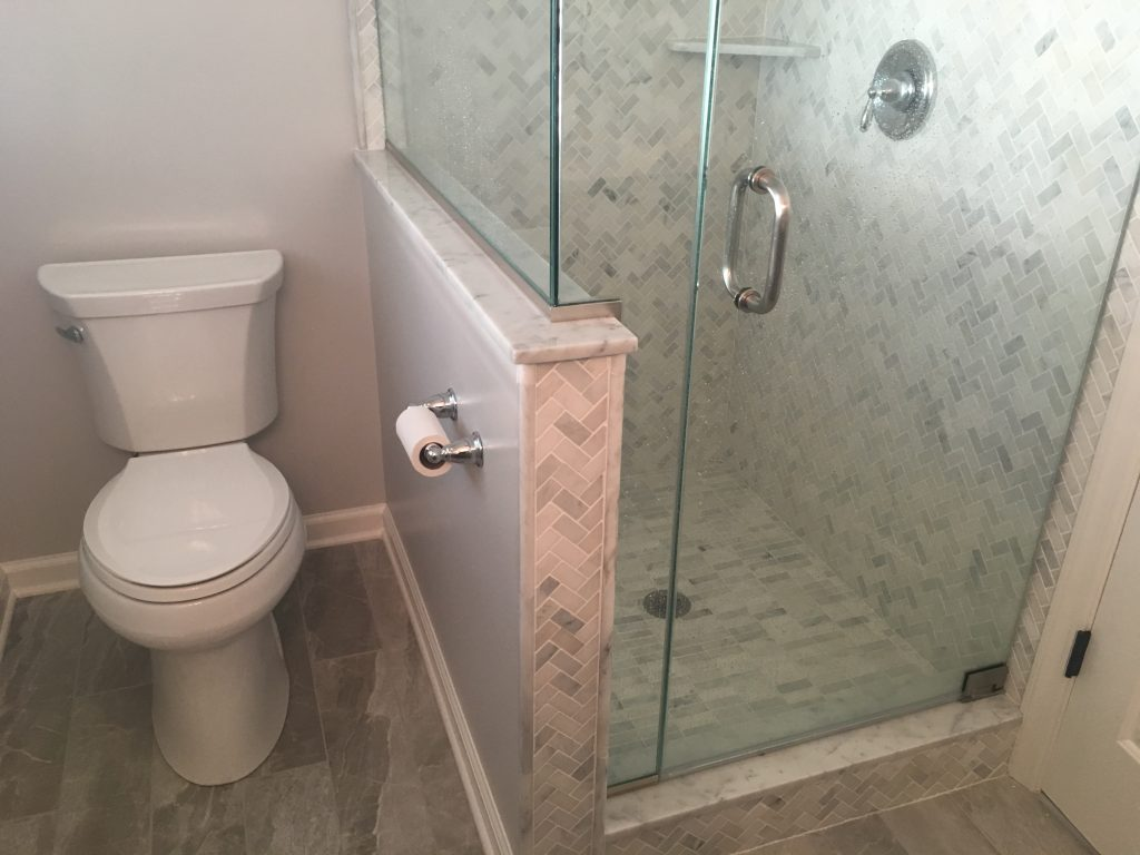 Master Bathroom Renovation with marble shower tile, wood-look tile, frameless shower door, knee wall to separate toilet