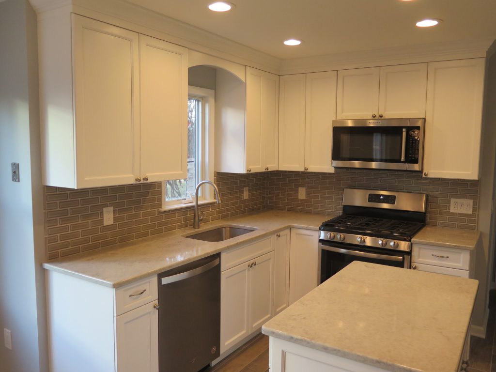 Kitchen Transformation - All new white cabinetry, quartz countertops, beveled backsplash, new window over sink