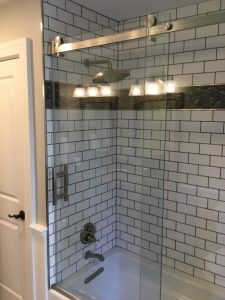 Remodeled Shower with Dark Grout and Glass Shower Door